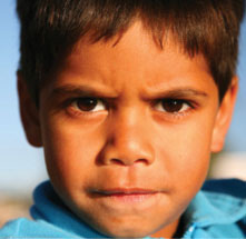 The stern face of a young indigenous boy