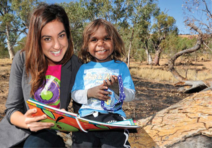 A smiling young woman with a smiling indigenous child looking up from a book they are reading